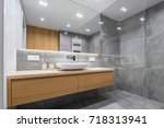 Modern bathroom with wooden countertop, shower, basin and big mirror - stock photo