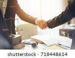 Stock photo handshake between attorneys and clients after agreeing to enter into a contract for a court case 718448614