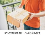 delivery man in orange uniform... | Shutterstock . vector #718485295