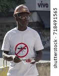Small photo of Rio de Janeiro, Brazil, February 13, 2016: man wearing mosquito-print shirt distributes pamphlets teaching how to eliminate mosquitoes Aedes Aegypti, transmitter of diseases like dengue and zika virus