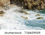rocky seashore with splashing... | Shutterstock . vector #718609009