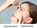 young woman applying eye lotion. | Shutterstock . vector #718635439