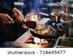 hands of cook frying vegetables ... | Shutterstock . vector #718645477