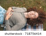 a curly young man lies on the... | Shutterstock . vector #718756414