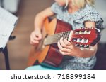little girl learning to play to ... | Shutterstock . vector #718899184