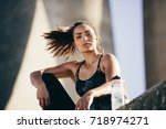 fit young woman sitting... | Shutterstock . vector #718974271