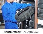 mechanic pulls tire from the... | Shutterstock . vector #718981267