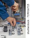 Small photo of Hands of electrician with screwdriver tighten up switching electric actuator equipment in fuse box
