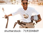smiling african man sitting on... | Shutterstock . vector #719204869