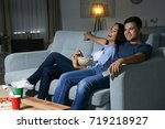 young couple watching tv in... | Shutterstock . vector #719218927