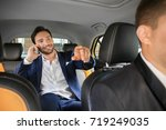 Small photo of Handsome man talking on phone while sitting in taxi car