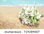 beautiful bouquet on sand.... | Shutterstock . vector #719289007