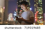 man looking at mobile phone  | Shutterstock . vector #719319685