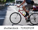 Small photo of Cyclist amateur and enthusiast in summer clothes and a bag behind his back prefers an ecologically clean and healthy bicycle type of transport crosses urban city street with cars flooded with sunlight