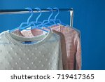 warm woolen sweaters hanging on ... | Shutterstock . vector #719417365