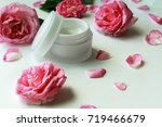Stock photo cosmetic cream container and pink rose flowers on white background opened jar of facial or body 719466679
