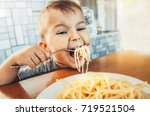 baby in the kitchen eagerly... | Shutterstock . vector #719521504