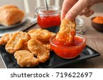 Person Dipping Chicken Nugget...