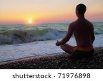Man in the meditation on the shore of the sea - stock photo