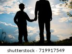 silhouette of father and son... | Shutterstock . vector #719917549