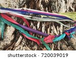 Small photo of An age-old tree and weathered colorful clothes in front of a temple in Thailand