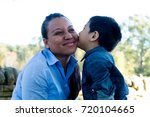 Latino Son Giving A Kiss To Hi...