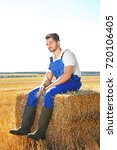 Small photo of Young male farmer sitting on pressed straw briquette in field