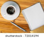 White cup of hot coffee and blank page note book on wood table with silver pen - stock photo
