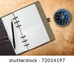 Black pen with Brown Leather cover note book and Compass on old map background - stock photo