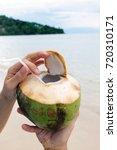 drinking fresh coconut juice on ...   Shutterstock . vector #720310171