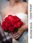 Stock photo bride holding beautiful and full red rose bouquet 720479449