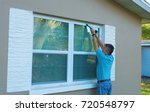 Small photo of Homeowner caulking window with a caulk gun, an important part of weatherproofing homes and houses against rain, wind, hurricanes and storms.