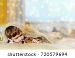 Stock photo cute baby embracing and sleeping under wool blanket in early morning christmas day 720579694