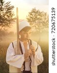Small photo of young man in traditional albanian costume playing flute in front of nature meadow and evening dusk