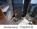 Small photo of Abseiler worker cleaning on rope, abseiling from height building in city of Sydney, Australia.