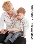 Small photo of Mother and baby embracing in affectionate moment, reading book.