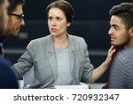 Small photo of Experienced psychologist putting her hands on shoulders of two rivals during session
