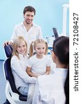 Young family with a child in the dental office - stock photo