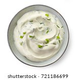 Bowl of sour cream sauce with herbs isolated on white background, top view