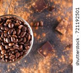 Small photo of Close up part of Full glass cup of Roasted coffee beans on the dark stone background with dissipate cocoa, pieces of chocolate and beans. Selective focus.Top view. Coffee love concept. Square shoot.