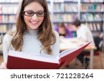 portrait of a woman in a library | Shutterstock . vector #721228264