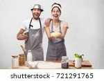 Small photo of Positive woman keeps fluffy dough, demonstrates culinary talent, going to bake pastry or rich roll, have all necessary ingredients on table, recieves help from best friend who is talented cooker