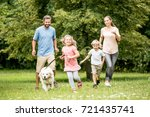 Stock photo family running with dog and having fun in summer 721435741