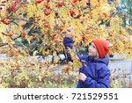 curious kid girl collects rowan ... | Shutterstock . vector #721529551