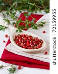 Heap of pink peppercorns on a wooden spoon. - stock photo