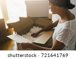 woman unpacking moving boxes...   Shutterstock . vector #721641769