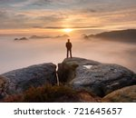 man stands alone on the peak of ... | Shutterstock . vector #721645657