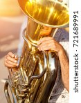 Small photo of old man playing tuba on street