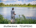 man fishing on a lake  | Shutterstock . vector #721693261