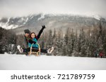 man pushing woman on sleigh in... | Shutterstock . vector #721789759